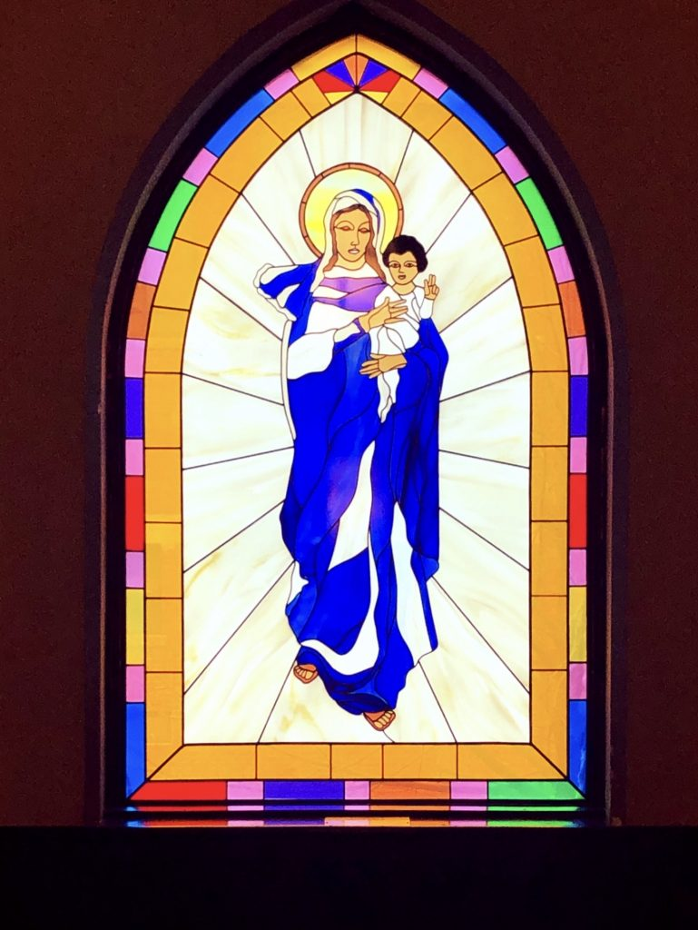 Stained glass window of Mary holding baby Jesus.